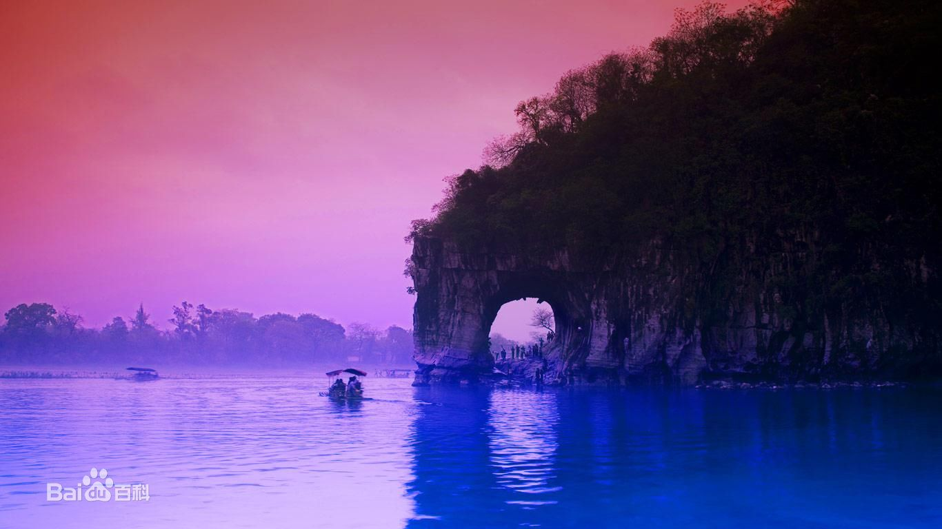 "The Elephant Trunk Hill (Chinese: 象鼻山; pinyin: Xiàngbí Shān) is a hill, landmark and tourist attraction in Guilin, Guangxi, China.  Elephant Trunk Hill is the symbol of the city of Guilin. It got its name because it looks like an elephant drinking water. The round opening that would be under the elephant's trunk is known as Water-Moon Cave because at night the reflection of the moon can be seen through the arch and it looks as if it is under the water and floating on the surface of the water at the same time. Elephant Trunk Hill and Water-Moon Cave are located at the confluence of the Taohua River and the Lijiang River.   Guilin is a prefecture-level city in the northeast of the Guangxi Zhuang Autonomous Region, China, situated on the west bank of the Li River, and bordering Hunan to the north. Its name means, ""Forest of Sweet Osmanthus"", owing to the large number of fragrant Sweet Osmanthus trees located in the city. The city has long been renowned for its scenery of karst topography and is one of China's most popular tourist destinations."