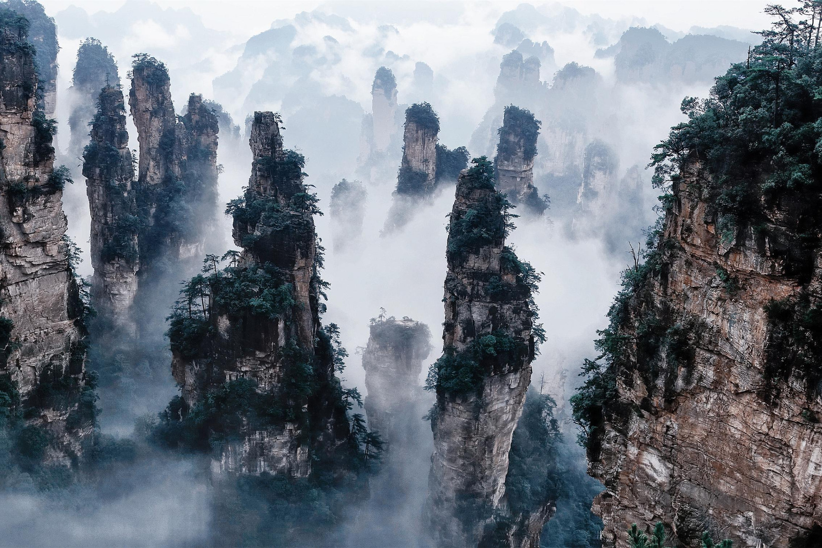 Picture from travelchina.  Zhangjiajie City features a variety of different terrains including: mountainous regions, upland areas, plains, and Karst rock areas. Among these, the mountains cover 76 percent of the total area. The world-famous natural heritage site 'Wulingyuan Scenic Area' is located on the base of these great mountains. Areas worth visiting include Zhangjiajie National Forest Park (known as China's first national forest park), Suoxiyu Natural Resource Reserve, and Tianzi Mountain Natural Resource Reserve. The scenic area hosts many natural features including: mountains, forests, caves, lakes and waterfalls and perhaps there are more than three thousand rock ridges and eight hundred ghylls. They enjoy the reputation of 'Original Picture on Mountain and River of China'. This wonderland is covered with dense forests and is considered Mother Nature's Oxygen Bar.