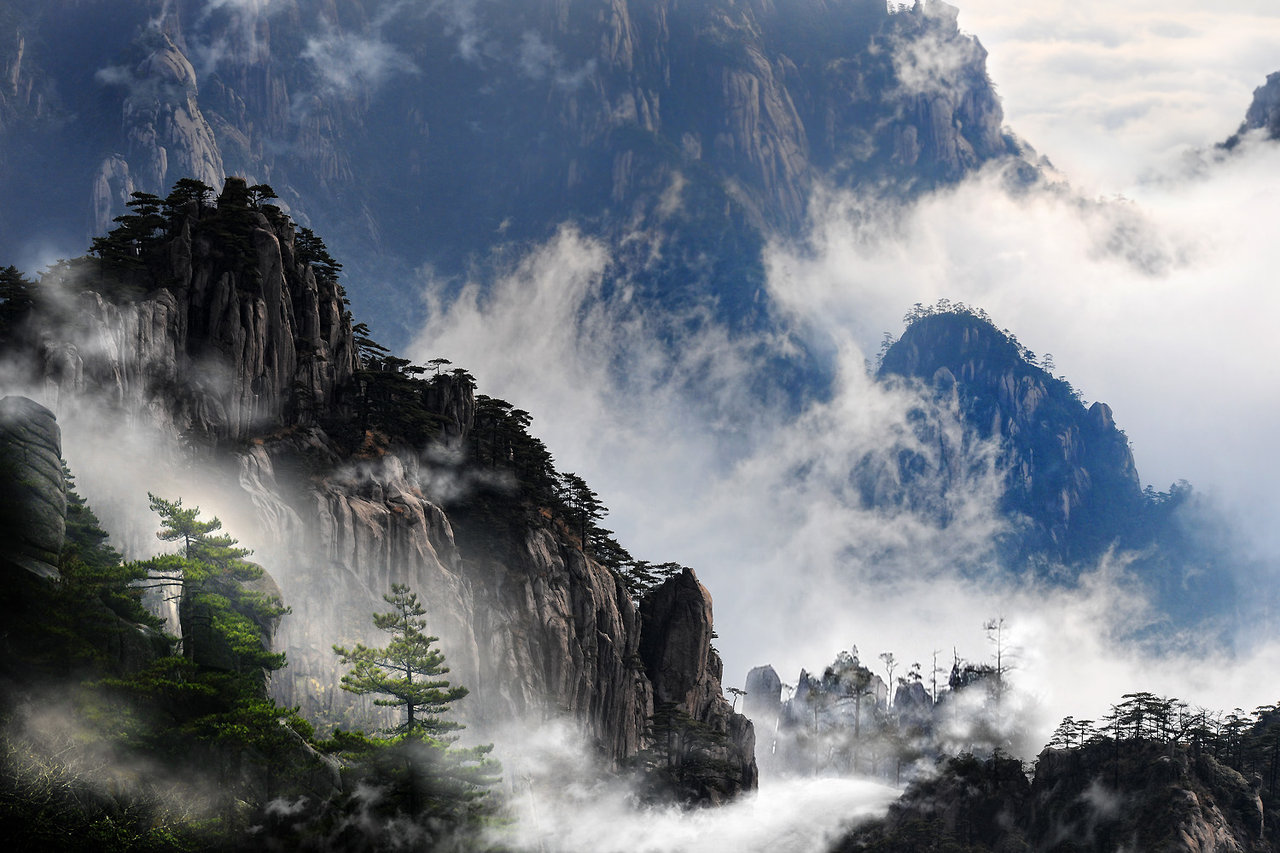 "Picture from deviantart. Huangshan (simplified Chinese: 黄山; traditional Chinese: 黃山; pinyin: Huángshān; literally: ""Yellow Mountains""), is a mountain range in southern Anhui province in eastern China. Vegetation on the range is thickest below 1,100 meters (3,600 ft), with trees growing up to the treeline at 1,800 meters (5,900 ft).  The area is well known for its scenery, sunsets, peculiarly shaped granite peaks, Huangshan Pine trees, hot springs, winter snow, and views of the clouds from above. Huangshan is a frequent subject of traditional Chinese paintings and literature, as well as modern photography. It is a UNESCO World Heritage Site, and one of China's major tourist destinations. Huangshan is also the famous place for Chinese high quality teas, such as Huangshan Maofeng, Keemun Black and Blooming Tea. The Huangshan mountain range has many peaks, some more than 1,000 meters (3,250 feet) high. The three tallest and best-known peaks are Lotus Peak (Lian Hua Feng, 1,864 m), Bright Summit Peak (Guang Ming Ding, 1,840 m), and Celestial Peak (Tian Du Feng, literally Capital of Heaven Peak, 1,829 m). The World Heritage Site covers a core area of 154 square kilometres and a buffer zone of 142 square kilometres.The mountains were formed in the Mesozoic, about 100 million years ago, when an ancient sea disappeared due to uplift. Later, in the Quaternary Period, the landscape was shaped by the influence of glaciers."