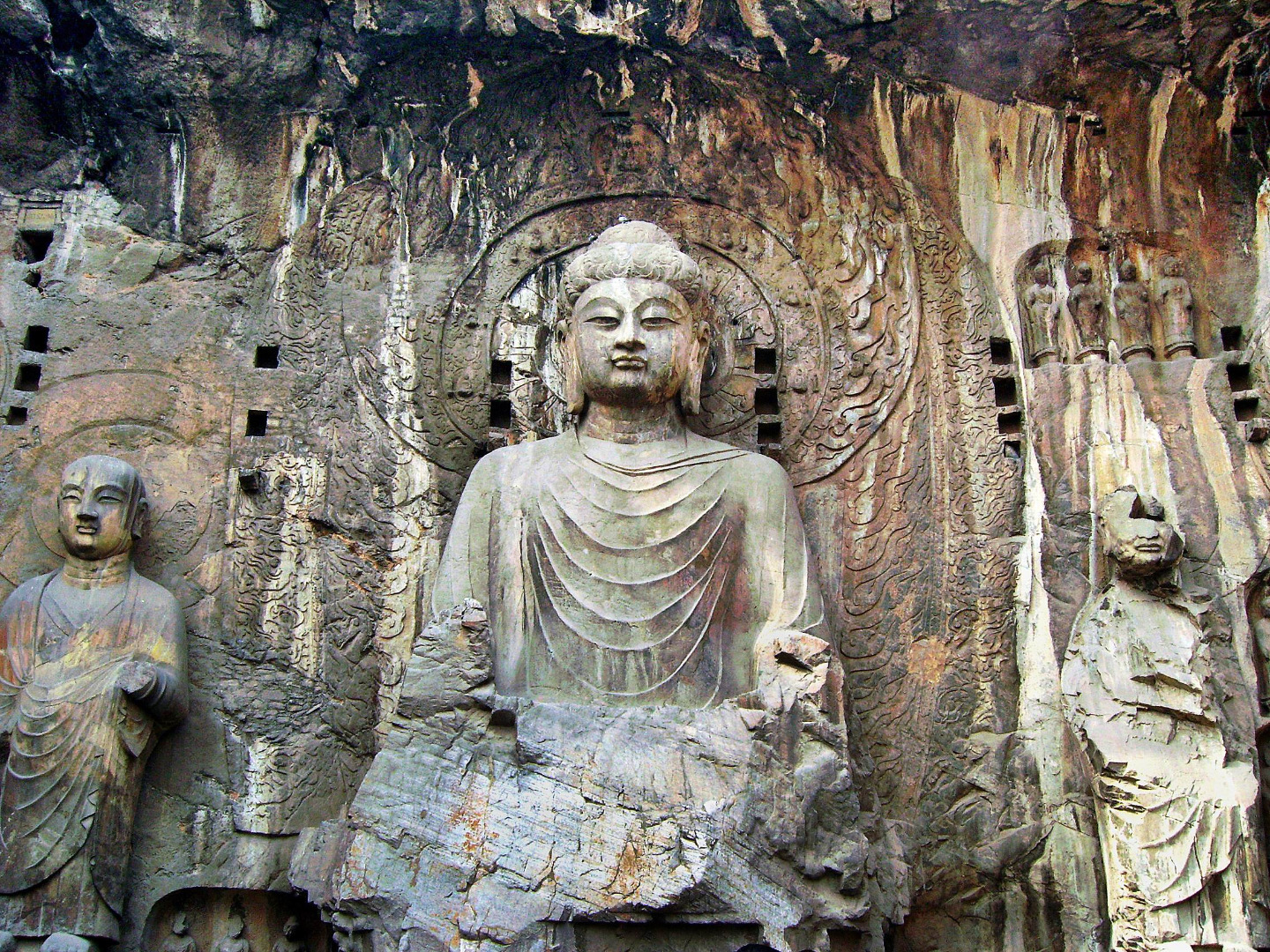 "Picture from globeimages. The Longmen Grottoes (simplified Chinese: 龙门石窟; traditional Chinese: 龍門石窟; pinyin: lóngmén shíkū; lit. Dragon's Gate Grottoes) or Longmen Caves are one of the finest examples of Chinese Buddhist art. Housing tens of thousands of statues of Buddha and his disciples, they are located 12 kilometres (7.5 mi) south of present day Luòyáng in Hénán province, China. The images, many once painted, were carved into caves excavated from the limestone cliffs of the Xiangshan and Longmenshan mountains, running east and west.  There are as many as 100,000 statues within the 1,400 caves, ranging from an 1 inch (25 mm) to 57 feet (17 m) in height. The area also contains nearly 2,500 stelae and inscriptions, whence the name ""Forest of Ancient Stelae"", as well as over sixty Buddhist pagodas. Situated in a scenic natural environment, the caves were dug from a 1 kilometre (0.62 mi) stretch of cliff running along both banks of the river. 30% date from the Northern Wei Dynasty and 60% from the Tang, caves from other periods accounting for less than 10% of the total. Starting with the Northern Wei Dynasty in 493 AD, patrons and donors included emperors, Wu Zetian of the Second Zhou Dynasty, members of the royal family, other rich families, generals, and religious groups.  In 2000 the site was inscribed upon the UNESCO World Heritage List as ""an outstanding manifestation of human artistic creativity,"" for its perfection of an art form, and for its encapsulation of the cultural sophistication of Tang China."