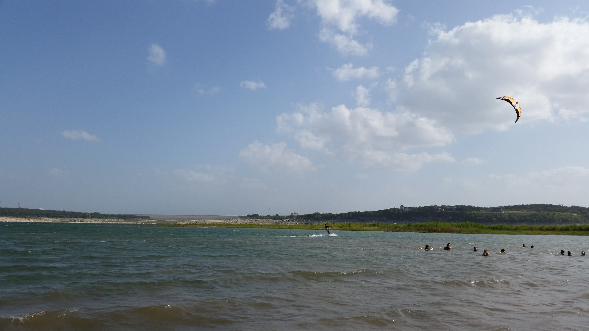 Surfing, swimming and kids playing